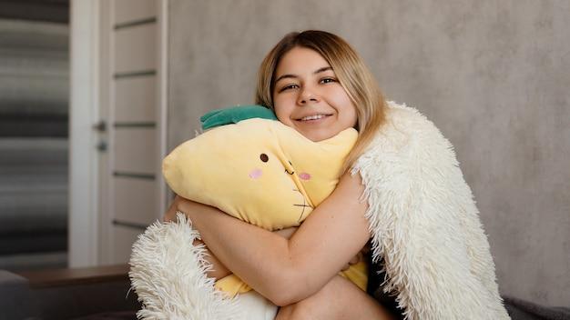 朝の白い毛布の下で幸せなブロンドは黄色い枕を抱きしめます。幸せな朝のコンセプト
