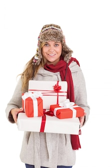 Happy blonde in winter clothes holding gifts on white background