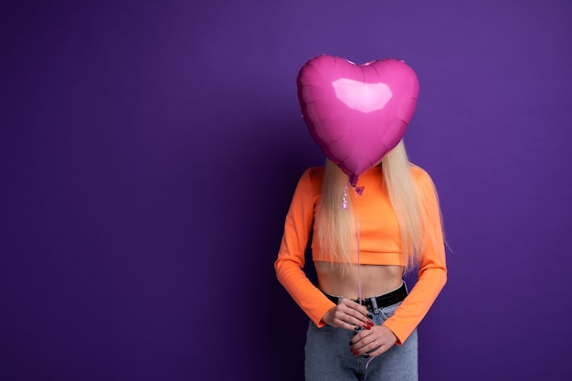 Счастливая блондинка с воздушными шарами в форме сердца на фиолетовом фоне в студии. день святого валентина 14 февраля.