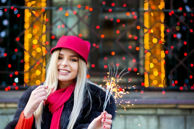 ぼやけた街の明かりで線香花火で新年を祝う幸せなブロンドの女性。テキスト用のスペース