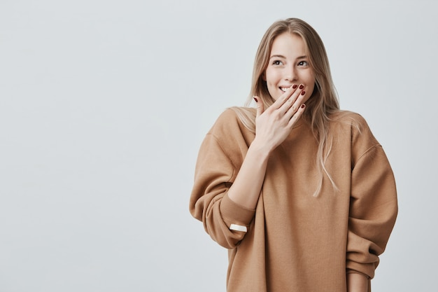 Happy blonde woman closing her mouth with hands going to see surprise prepared by husband standing and smiling