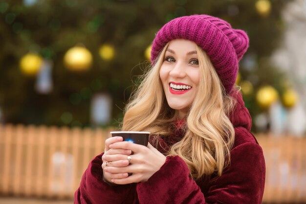 冬の服を着て、通りでコーヒーを飲む幸せなブロンドの女性