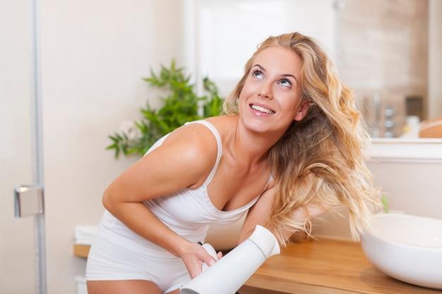 Счастливая блондинка сушка волос в ванной комнате