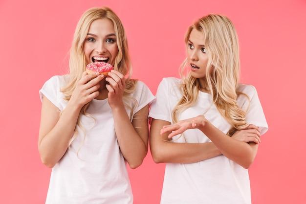 Счастливая блондинка ест пончик и смотрит вперед, в то время как ее недовольная сестра смотрит на нее через розовую стену