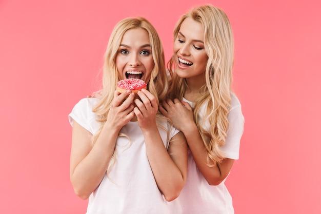 Счастливая блондинка ест пончик, пока ее сестра стоит за ней над розовой стеной