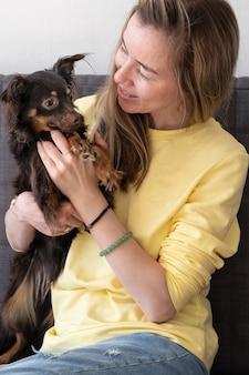Счастливая белокурая женщина обнимает смешной коричневый русский той терьер. концепция ухода за домашними животными. любовь и дружба