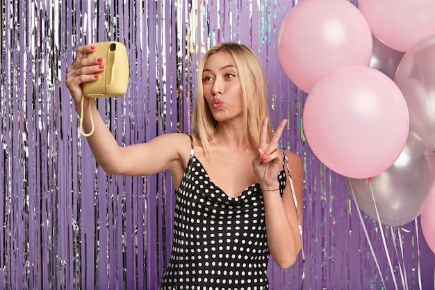 Счастливая блондинка с макияжем, скрещенными губами, делает селфи с маленькой камерой, стоит у стены, украшенной воздушными шарами и мишурой, носит стильное платье, показывает жест рукой мира.