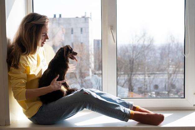 Счастливый белокурая женщина держит коричневый русский той терьер. сядьте на подоконник. концепция ухода за домашними животными.
