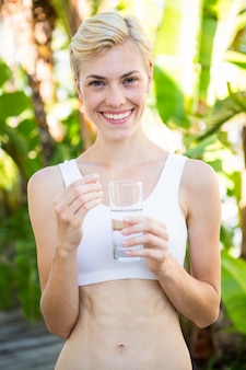 Happy blonde woman holding pill and glass of water