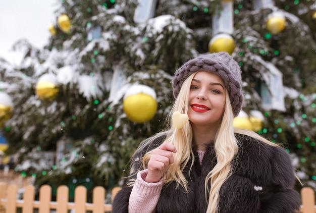街のクリスマスツリーに対しておいしいチョコレート菓子を保持している灰色のニット帽の幸せなブロンドの女性