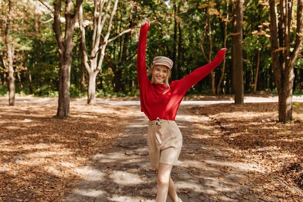 秋の公園で踊る素敵な赤いセーターとベージュのショートパンツで幸せなブロンドの女性。スタイリッシュな若い女性は、屋外の良いweaterで喜びを持ってポーズをとっています。