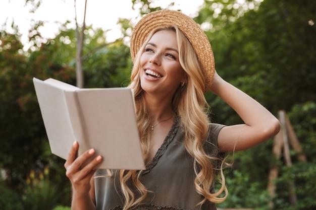 밀짚 모자 책을 들고 야외 벤치에 앉아있는 동안 멀리 찾고 행복 금발의 여자