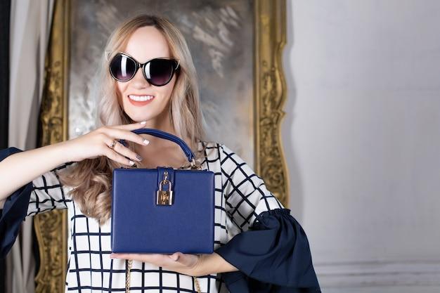 青い革の財布を保持しているサングラスで幸せなブロンドの女性。テキスト用のスペース