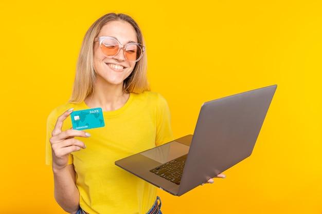 Счастливая белокурая женщина в футболке с портативным компьютером и кредитной картой над желтым.