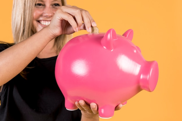 Happy blonde woman inserting coin inside pink piggy bank