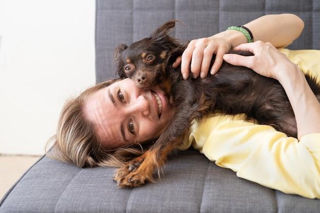 Счастливая белокурая женщина, лежащая с забавным коричневым русским игрушечным терьером на диване. концепция ухода за домашними животными.