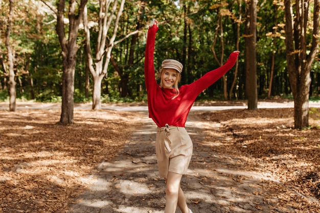 Happy blonde woman in nice red sweater and beige shorts dancing in autumn park. stylish young woman posing with joy in good weater outdoor.