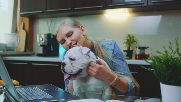 Happy blonde woman scratching the neck of bulldog puppy sitting in front of laptop in the kitchen