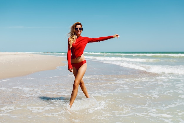 Happy blonde woman in seashore smiling happy. summer holidays concept. amzing tropical beach. wearing red bikini. perfect tan body and slim figure.