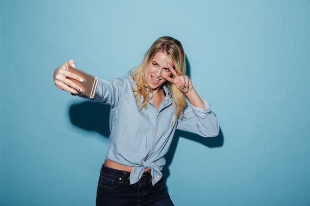 Donna bionda felice in camicia che fa selfie sullo smartphone