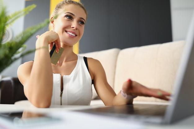 彼女の手にクレジットカードを持ってラップトップのそばに座っている幸せなブロンドの女性女性はクレジットカードを入力します
