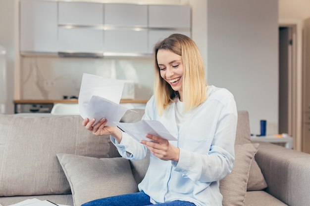 Happy blonde woman sitting at home on the couch, happy with timely payment of credit bills and closing the credit line, received good news from the bank