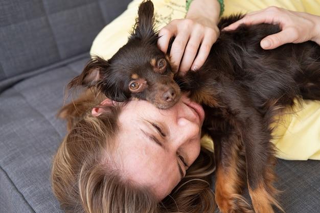 Счастливый белокурый сон женщины с забавным коричневым русским игрушечным терьером на диване. концепция ухода за домашними животными.