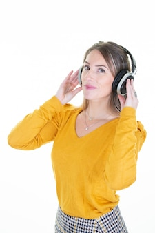 Happy blonde woman smiles with headphones on head looking camera dressed in yellow shirt isolated on white