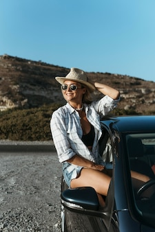 Happy blonde woman standing out of car window