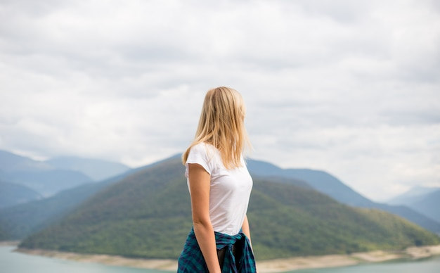 Happy blonde woman stands on the wall of mountain peaks. ecotourism, travel concept and discovery of beautiful places