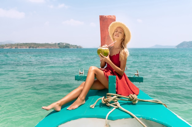Happy blonde woman traveler in red dress and straw hat relaxing  with coconut on boat