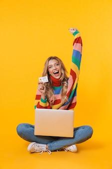 Счастливая блондинка женщина с помощью портативного компьютера и кредитной карты, сидя на полу, изолированном над желтой стеной
