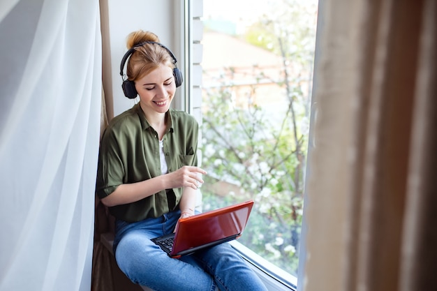 A happy blonde woman using a laptop computer to video call friends and parents, sitting at home on the window,