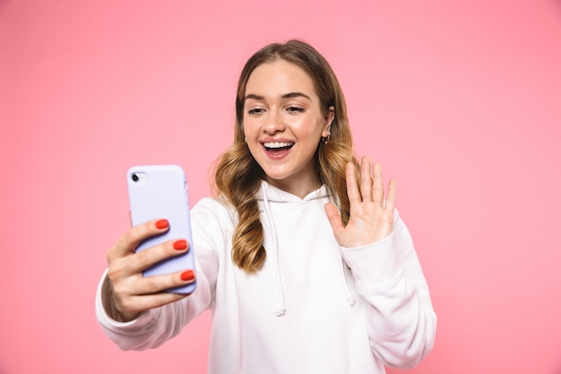 ビデオ通話で話し、ピンクの壁の前で手を振ってカジュアルな服を着て幸せなブロンドの女性