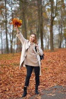トレンディな秋のコートと黒のジーンズを着て幸せな金髪女
