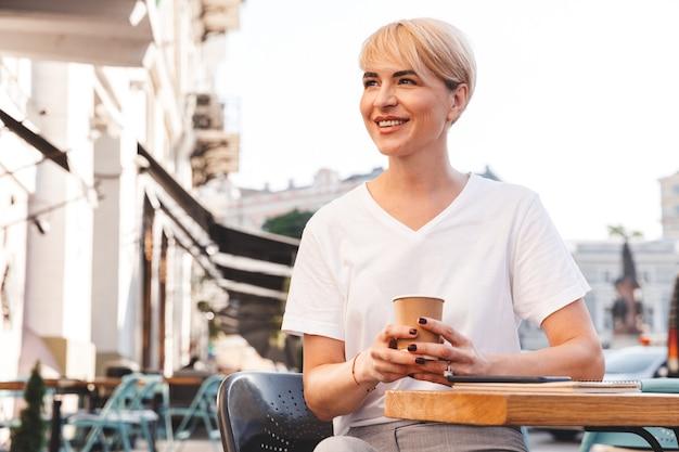 夏にストリートカフェに座って、紙コップからコーヒーを飲む白いtシャツを着て幸せなブロンドの女性