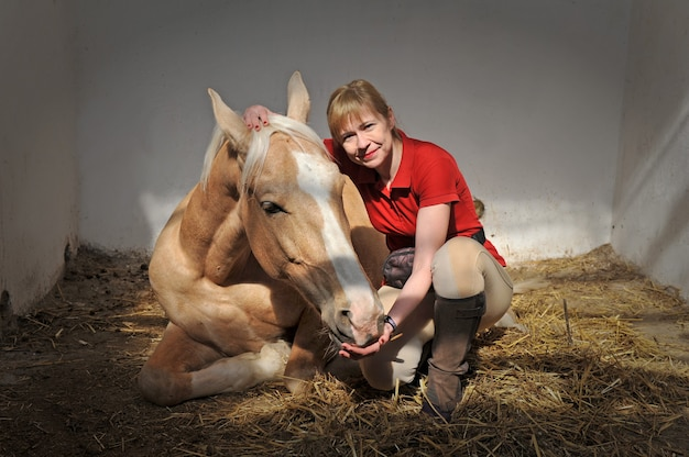 Happy blonde woman with a blond horse lying in a stable on the ranch at day time.
