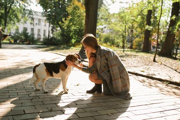 Счастливая блондинка с собакой в парке в солнечный день