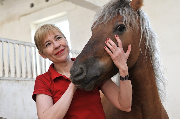 Happy blonde woman with a horse in a stable on the ranch.