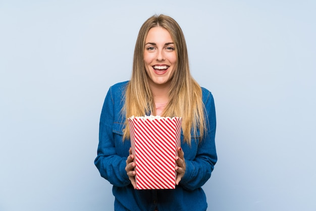 Happy blonde woman with popcorns over blue wall