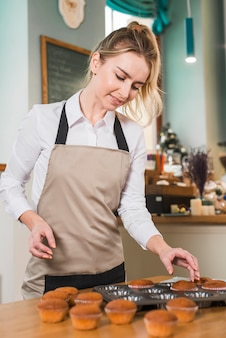 Happy blonde young woman removing the muffin from baking mold