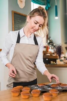 Счастливая белокурая молодая женщина извлекая булочку от формы для выпечки