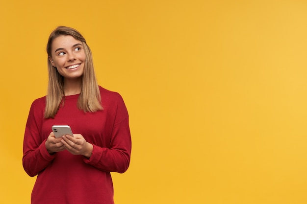 Happy blonde young woman, smiling, keeps mobile phone in hands, looking with curiosity dreamily to the right on free copy space, standing on the left side