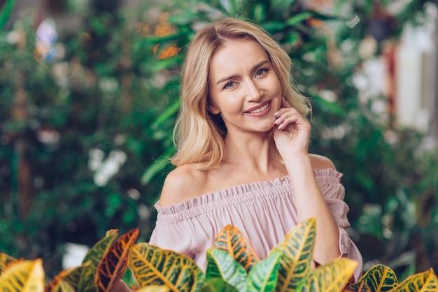 庭に立っている幸せな金髪若い女