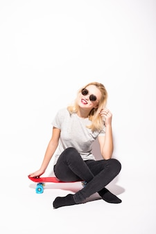 Happy blondie with crossed legs sits on red skateboard in front of white wall