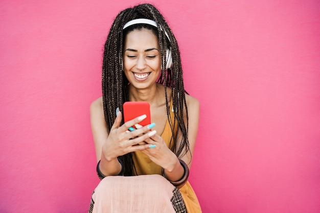 Счастливая богемная женщина-влиятельная женщина, слушающая музыку из плейлиста с розовым фоном - сосредоточьтесь на лице