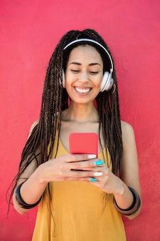 분홍색 배경으로 재생 목록 음악을 듣는 행복한 보헤미안 인플루언서 여성 - 얼굴에 집중