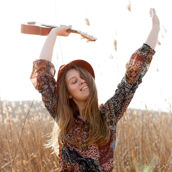 Happy bohemian woman posing while holding ukulele