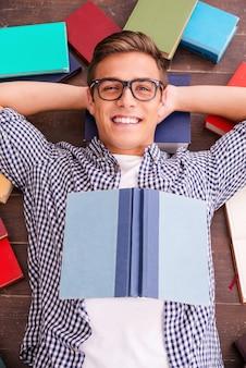 Счастливый книжный червь. вид сверху счастливого молодого человека, держащего руки за головой и улыбающегося, лежа на деревянном полу с разноцветными книгами, лежащими вокруг него