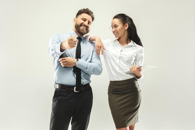 幸せなボス。男と彼の秘書が事務所に立っています。